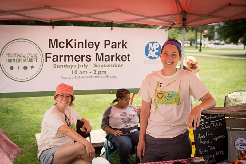 McKinley Park Advisory Council members, including Katie Flores, left, and Samantha Hertel, right, man the booth at the McKinley Park Farmers Market.
