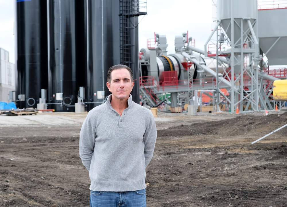 MAT Asphalt owner Michael Tadin Jr. stands in front of the new asphalt plant, slated to open this month.