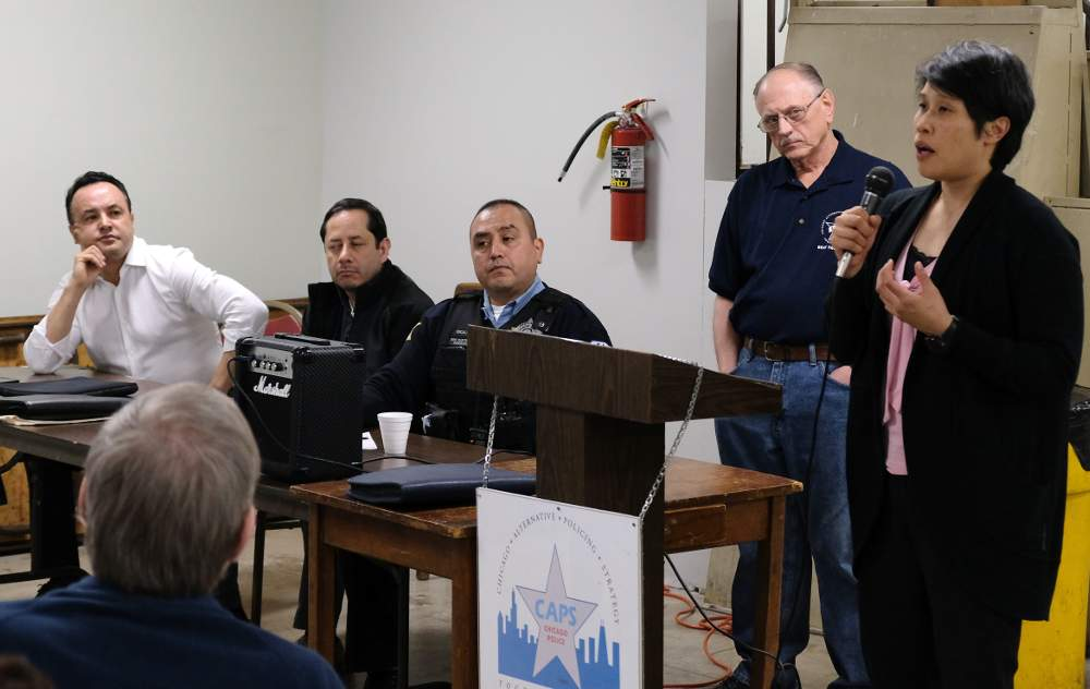 Vernalynn De La Rosa speaks of her coalition's program to combat teen drinking while, from left, 12th Ward Alderman George Cardenas, Chicago Police Department Community Organizer Holger DelCid, officer Oscar Escalante and Beat Facilitator Glenn Young look on.