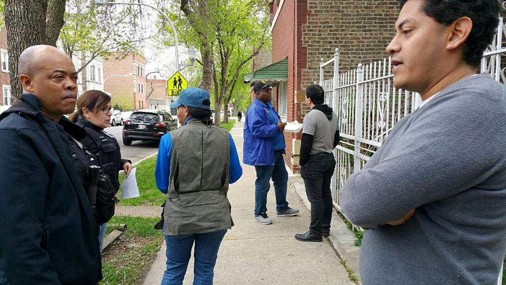 Chicago Police Department officers, inspectors from the Department of Buildings and 12th Ward Chief of Staff Samie Martinez, right, coordinate the Friday, May 11, house inspection with landlord Julio Zamudio, center-right.