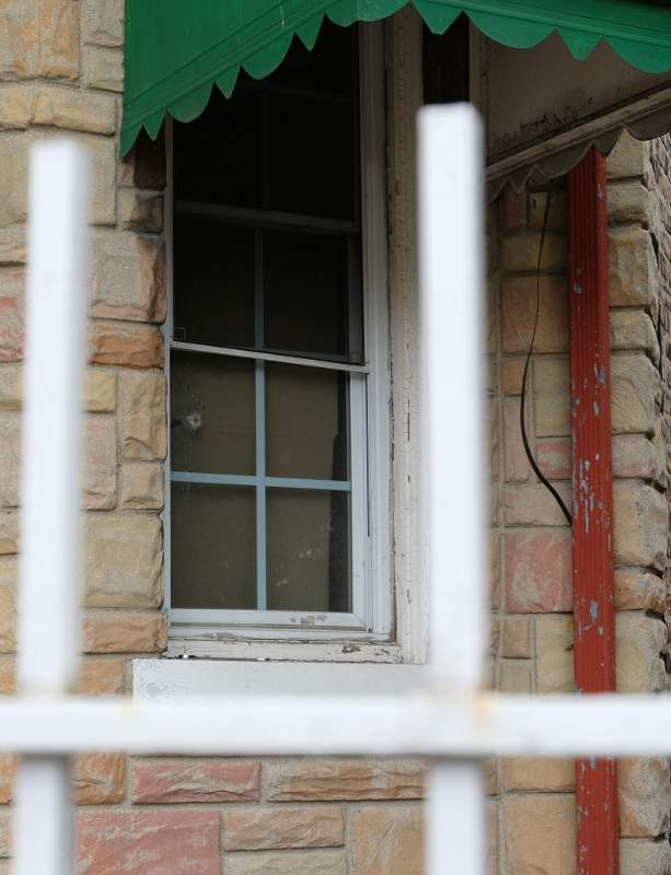 A front window at 3629 S. Wood St. reveals a bullet hole on the day of the inspection.