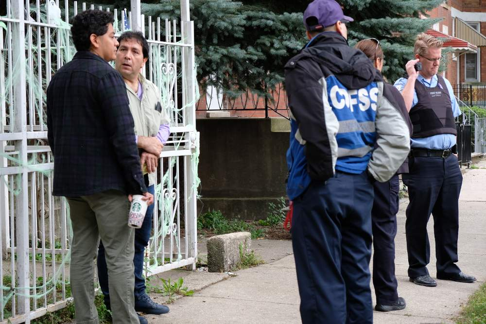 12th Ward Chief of Staff Samie Martinez, left, speaks with landlord Julio Zamudio on October 1 as social services and police personnel await the start of the eviction.