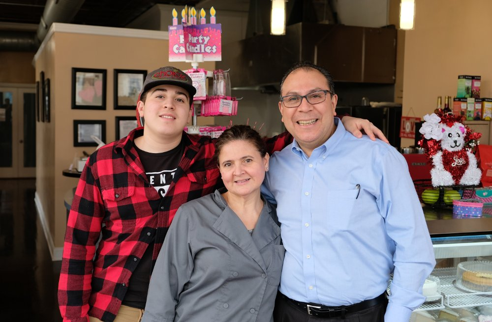 Cristina and Carlos Chavarria stand with their son, Kristoffer, in the front of the namesake shop Kristoffer's Cakes, a new business in the McKinley Park neighborhood.