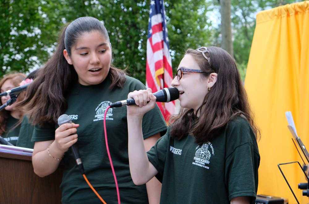 Dayanara Macedo, left, and Emily Tweedy from the school band Seven Miles belt out a tune at the assembly on Tuesday, June 11. at Evergreen Academy Middle School.