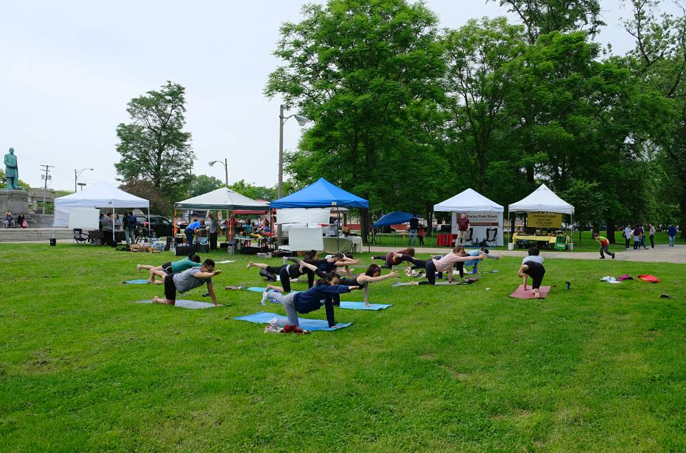 Yoga practitioners hold a position at the McKinley Park farmers market on Sunday, June 9. Yoga takes place every week at the market starting at 10 a.m. Photo by Queenie Chong.