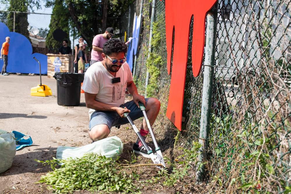 Local artist Juan Chavez trims back weeds and branches during the Marshfield Courts clean-up on Saturday, July 13.