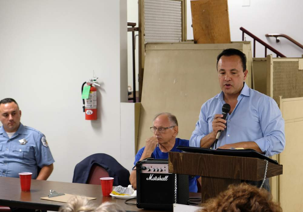 12th Ward Alderman George Cardenas discusses moving a police security camera to Hoyne Park alongside Officer Jason Solis and Beat Facilitator Glenn Young at the Wednesday, August 14, meeting for CAPS Beat 912.