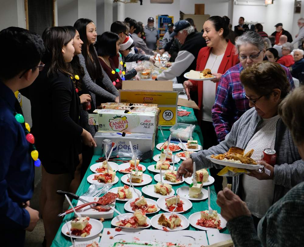It's all smiles as diners load up with the help of Evergreen Academy Middle School Students at the CAPS Beat 912 holiday party, held on Wednesday, December 11, at St. Maurice Church hall.