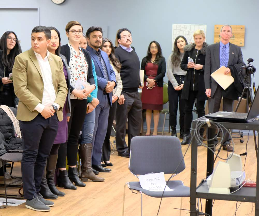 A cadre of elected officials, their representatives and community members stand when asked whether they oppose the MAT Asphalt permit at the town hall meeting on Thursday, January 16, at the National Latino Education Institute