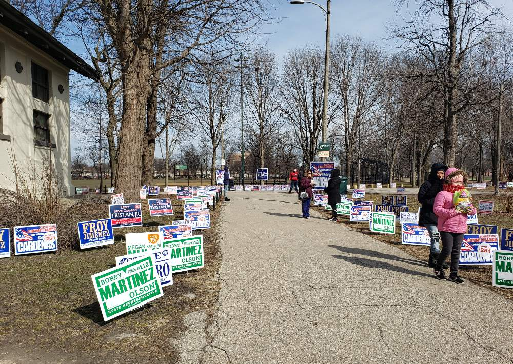 A gantlet of candidate signs and campaign advocates line the McKinley Park path leading to early voting, which takes place in the field house all week and weekend.