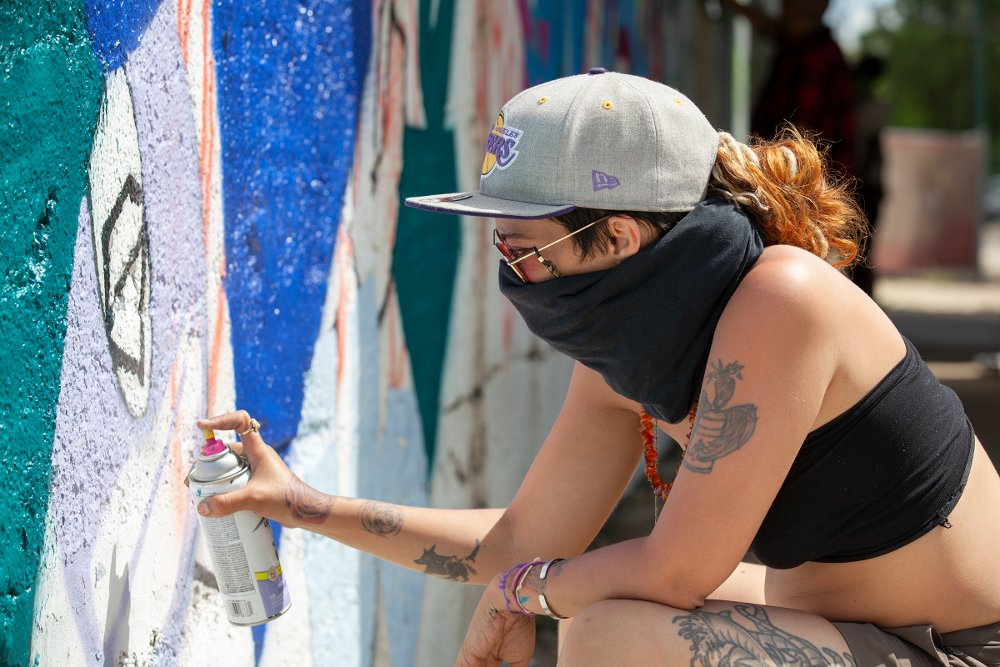 Graffiti artist Anias Machin creates a mural under the Orange Line viaduct on the 3400 block of South Hoyne Avenue on Monday, May 25th.  (Julie Jaidinger/McKinley Park News)